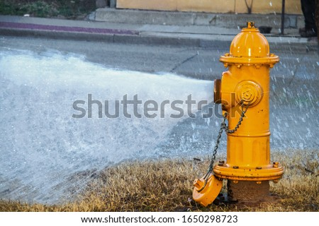 Yellow fire hydrant wide open gushing water onto the street with slightly grainy effect where water is falling back down over the pavement ストックフォト ©