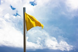 Yellow flag warning of medium danger on the beach. The flag on the flagpole flutters in the wind against the blue sky and white clouds in summer. . High quality photo