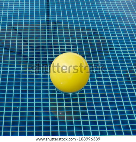 Yellow float ball on the swimming pool made of blue mosaic tiles