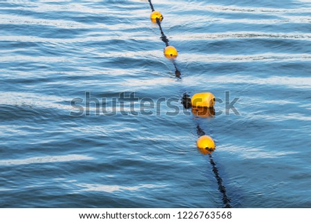 Yellow float floats on a rope floating in the sea #1226763568