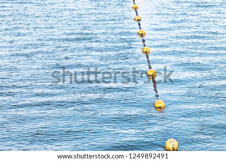 Yellow float floats on a rope floating in the sea #1249892491