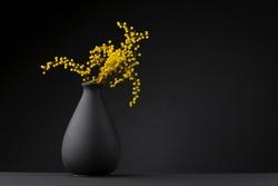 yellow flower on the black vase