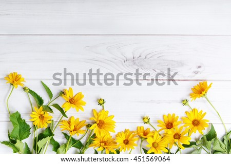 Yellow flowers on light wooden background. High top view. #451569064