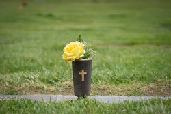 Yellow flowers set at graveside in memorial cemetery in California.