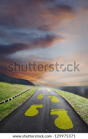 Yellow footprint on an asphalt road leading into the horizon of an apocalyptic cloudy sky.