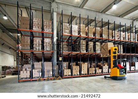 Yellow fork lifter work in big warehouse - stock photo