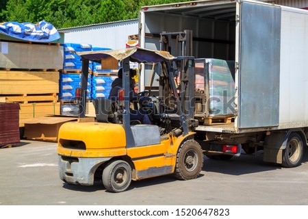 Yellow forklift loader loads cargo into truck for delivery to customers #1520647823