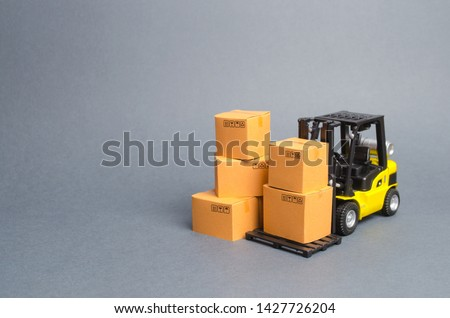 Yellow Forklift truck with cardboard boxes. Service storage of goods in a warehouse, delivery and transportation. Freight shipping, delivery. Import and export, commodity exchange with other countries