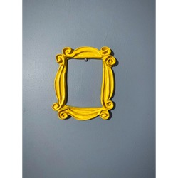 Yellow frame from the television show FRIENDS which was used around Monica's peep hole on the door. Purple wall. Picture frame. FRIENDS tv show frame