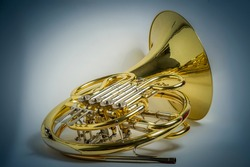 Yellow full double Bb\F French horn brass wind musical instrument on a white background with blue colored vignette