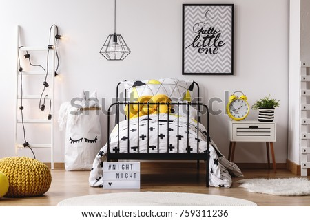 Yellow funny clock and plant on nightstand in white child's bedroom with yellow pouf on wooden floor #759311236