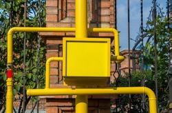 Yellow gas meter box with pipes and valves outdoors. Anti-vandal metal box, gas equipment. Copy space for text