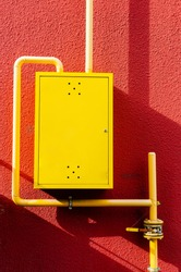 yellow gas pipe with a crane goes along the facade of a new multi-storey building. Distribution box for gas equipment