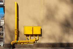 Yellow gas pipes with two closed junction boxes on the wall of the building. Energy supply in an apartment building