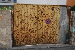Yellow gate riddled with bullets from the gun during the Balkan War