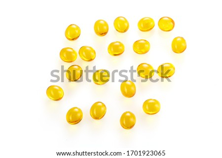 Yellow gel capsules pills. Capsules with yellow medicine on isolated white background. A lot of capsules vitamin D close-up. Bright oil yellow pills. Foto d'archivio ©