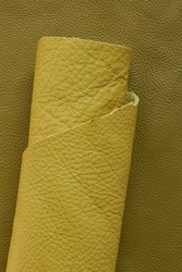 Yellow genuine leather roll.real leather. Leather in rolls on a dark beige leather surface.Hobby and craft material.Material for shoes and accessories