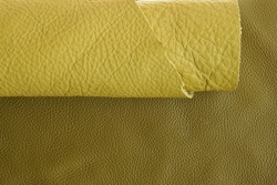 Yellow genuine leather roll.real leather set. Leather in rolls on a dark beige leather surface