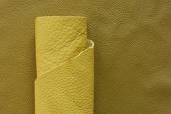Yellow genuine leather roll.real leather set. Leather in rolls on a dark beige surface.Hobby and craft material. leather texture close-up.Material for shoes and accessories