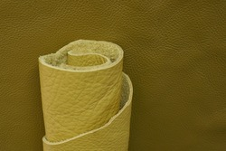 Yellow genuine leather roll.real leather set. Leather in rolls on a dark beige  surface.Hobby and craft. leather texture close-up.Material for shoes and accessories