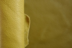 Yellow genuine leather roll.real leather set. Leather in rolls on a dark beige surface.Hobby and craft material. leather texture
