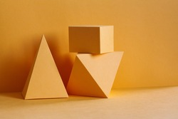 Yellow geometrical platonic solids figures still life composition, simplicity concept. Three-dimensional prism pyramid rectangular cube objects on yellow background