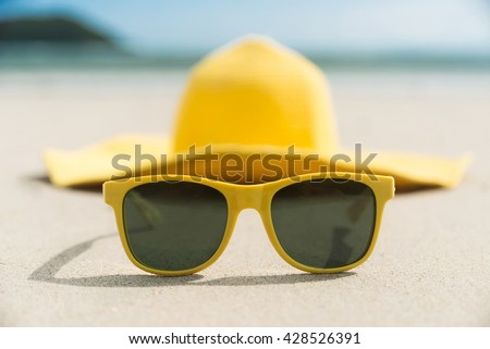 Yellow glasses and hat on the beach