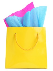 Yellow glossy shopping bag with pink and blue wrapping paper in it, isolated on white