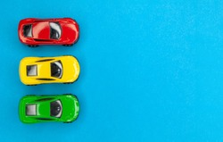 Yellow, green and red toy cars on a blue background, top view.