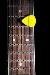 Yellow guitar pick on the fingerboard close up isolated on black background