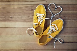 yellow gym shoes on a wooden floor, in which the laces are in the form of heart