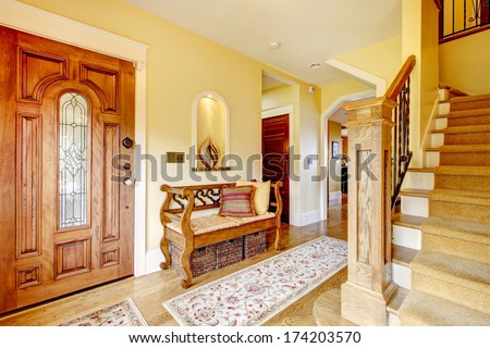Yellow hallway with hardwood floor, stairs and rustic wood hallway storage seat #174203570