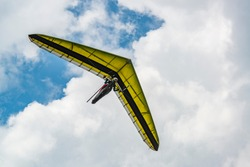 Yellow hang glider wing with cloudy sky on the background. Hangglider pilot and his aircraft.