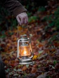 Yellow hanging lantern in hand at night. Close up.