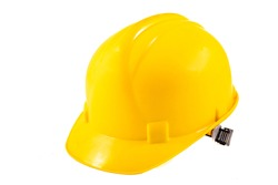 Yellow hard hat for construction workers. Protective clothing and accessories for employees. Light background.