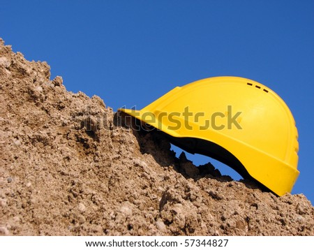 Yellow hard hat on the sandpile against the blue sky