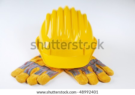 Yellow hard hat on the working gloves