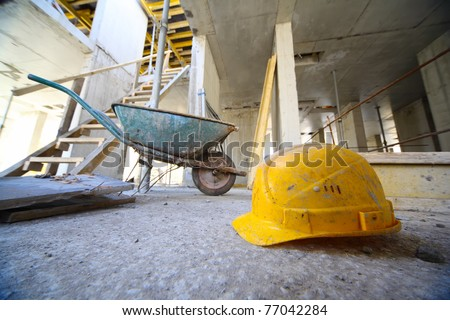Yellow hard hats and small cart on concrete floor inside unfinished building - stock photo