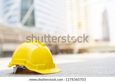 yellow hard safety wear helmet hat in the project at construction site building on concrete floor on city with sunlight. helmet for workman as engineer or worker. concept safety first.  #1378360703