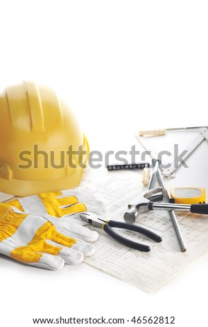 Yellow hardhat,  gloves and  hammer on drawings