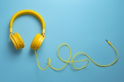 Yellow headphones on blue background. Music concept.