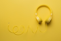 Yellow headphones on yellow background. Music concept.