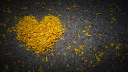 Yellow heart made of flower petals on dark background with space for text, heart shape, the concept of mourning, grief or sorrow.