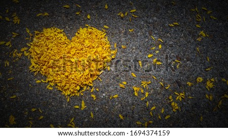 Yellow heart made of flower petals on dark background with space for text, heart shape, the concept of mourning, grief or sorrow. ストックフォト ©