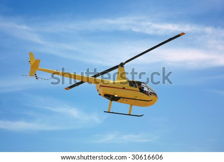 Yellow helicopter flying in a natural blue sky background with a photographer on board