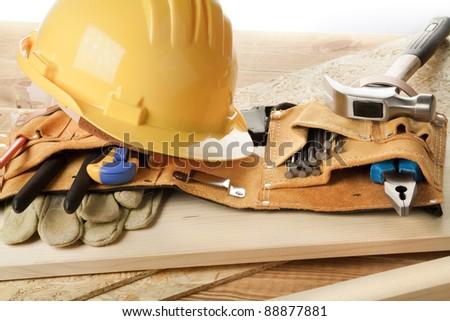 Yellow helmet and tool belt.