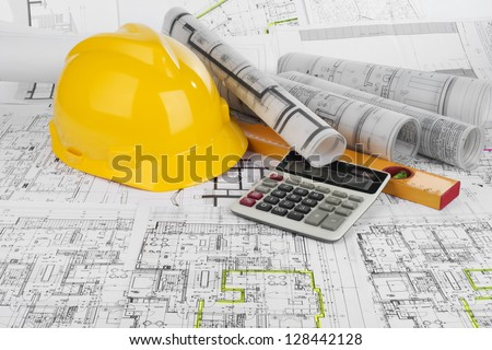 Yellow helmet, calculator, level and project drawings stock photo