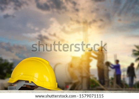 yellow helmet in construction site and construction site worker background safety first concept