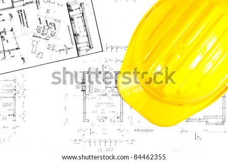Yellow helmet of an engineer with plans