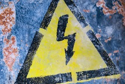 Yellow high current danger sign with a black arrow on the wall